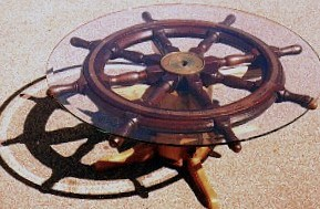 A table top made from a ships wheel and a Glass top
